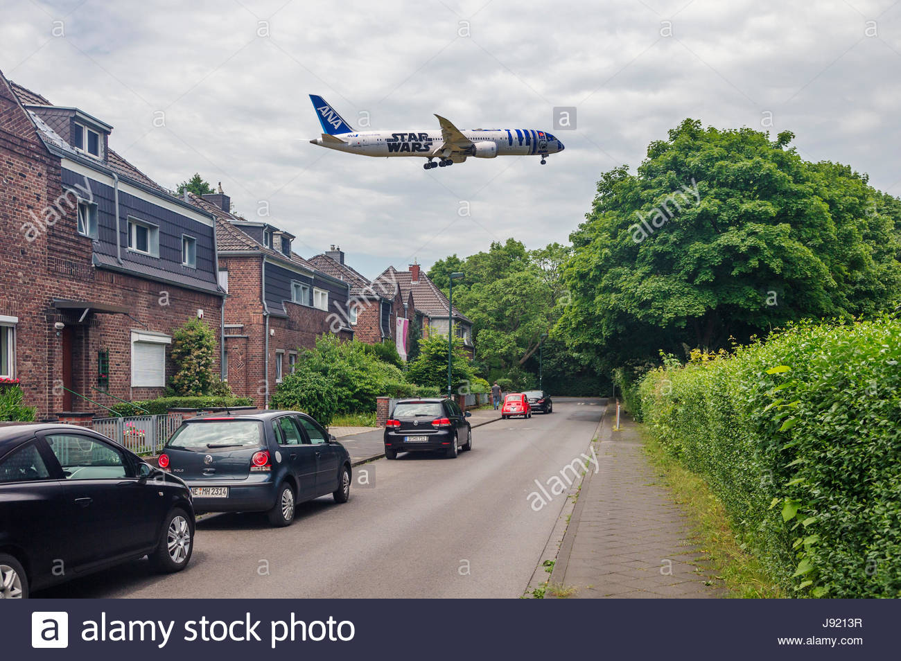 ANA Boeing 787-9 Dreamliner Starwars character R2-D2 livery over suburban residential area suburb housing buildings - Stock Image