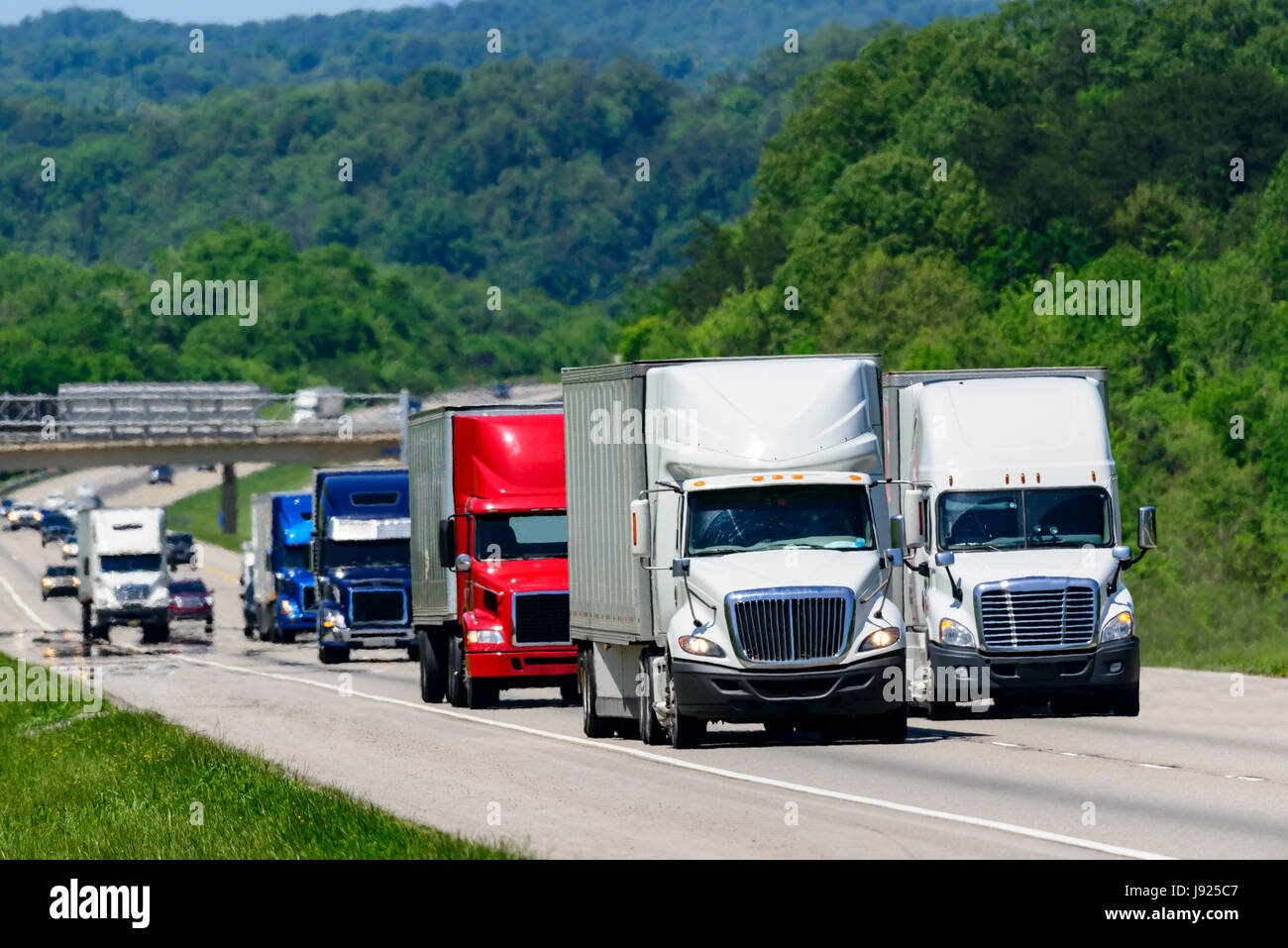 A squadron of eighteen-wheelers lead the way down an interstate highway in eastern Tennessee.  Heat waves rising - Stock Image