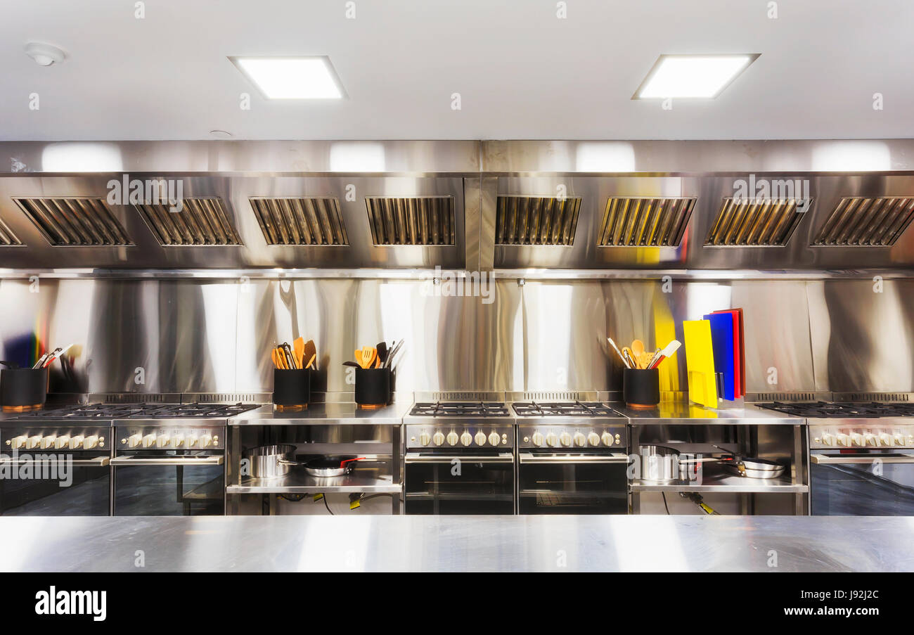 Modern clean equipped kitchen with stainless steel cook tops, cooking tables, utensils and small appliances. - Stock Image