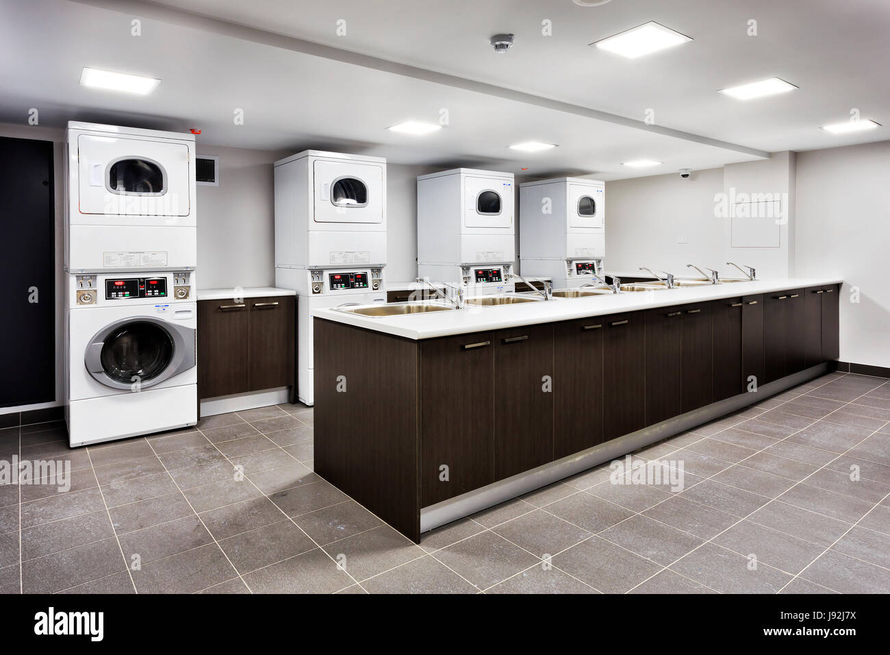 Powerful laundry machines and automatic dryers in big laundromat with a cupboard sinks for rinsing and tap water. - Stock Image