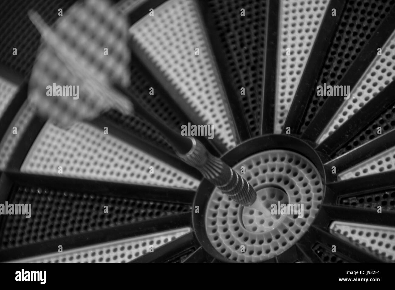 Black and white dart in the center of the dartboard target. Close up - Stock Image