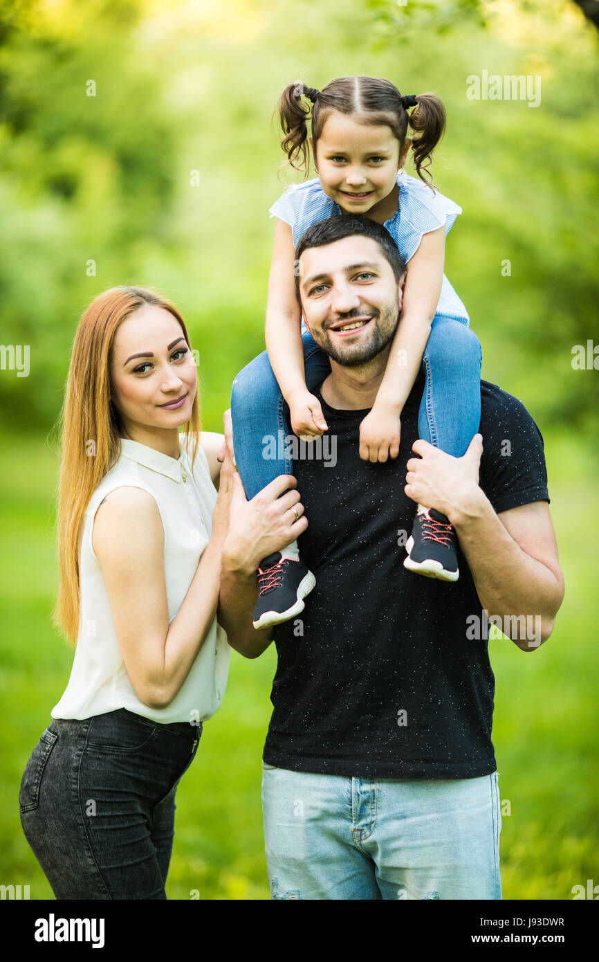 Young family of three having fun together outdoor. Pretty little daughter on her father back. Father carrying daughter Stock Photo