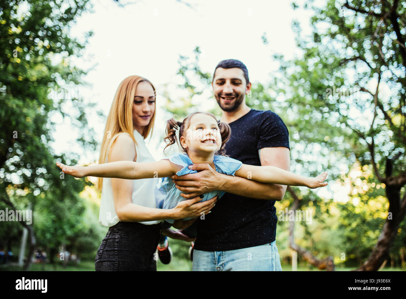 Happy joyful young family father, mother and little daughter having fun outdoors, playing together in summer park. - Stock Image