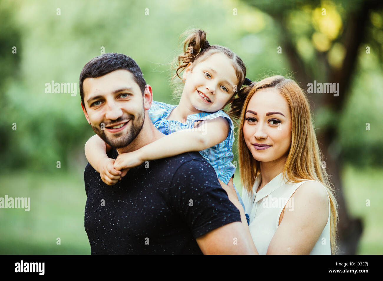 Happy joyful young family father, mother and daughter having fun outdoors, playing together in summer park, countryside. - Stock Image