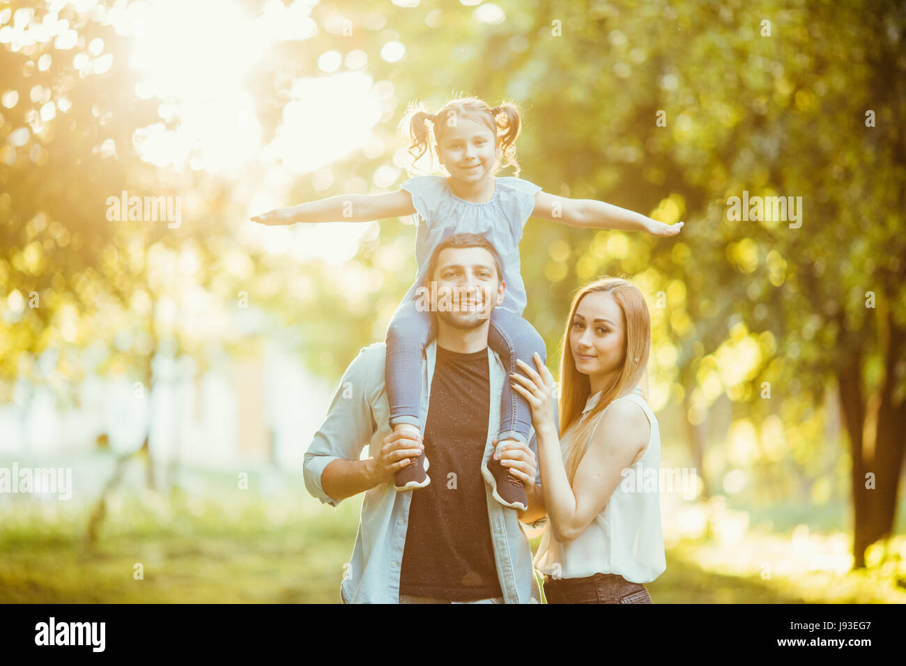 family Mom and Dad holding daughter on his back and have fun in the park. - Stock Image