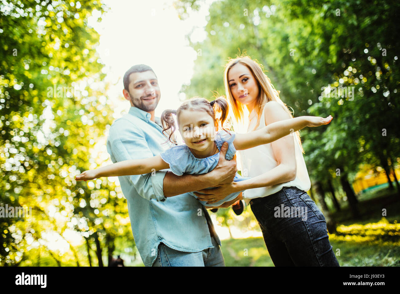 Happy family with one child having fun together in summer city park Stock Photo