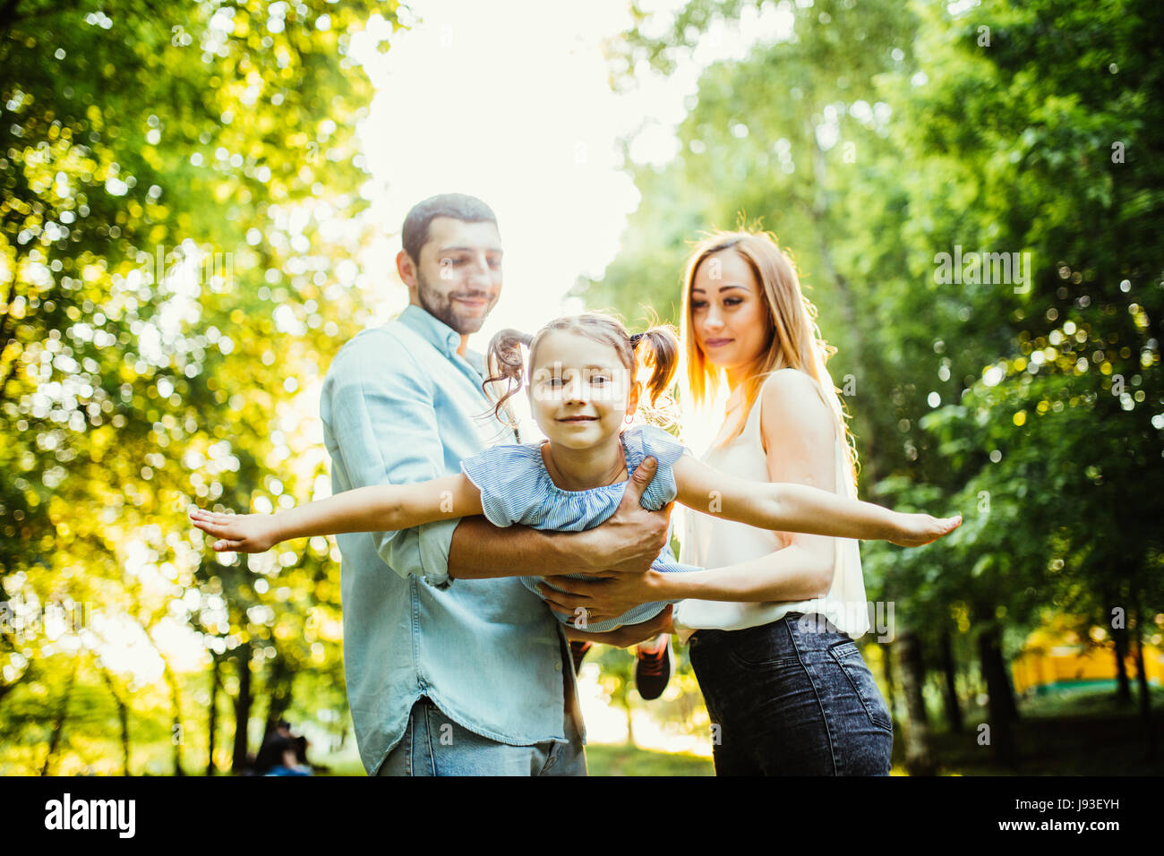 Happy family with one child having fun together in summer city park - Stock Image