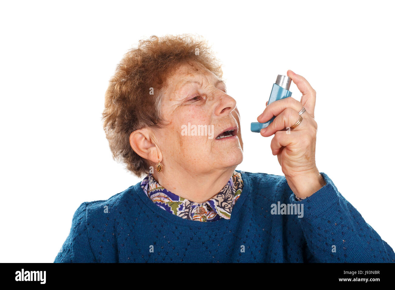 Picture of an elderly woman using an inhaler beacuse of an asthma attack - Stock Image