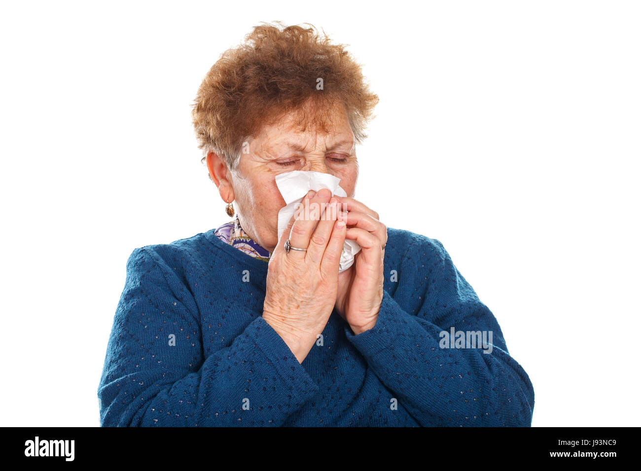 Picture of an elderly woman blowing her nose - isolated background - Stock Image