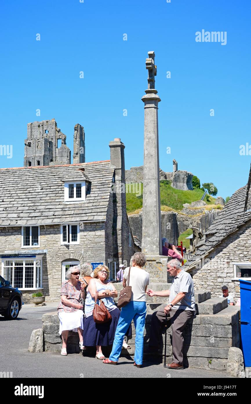Tourists around the stone cross in the village centre with the castle to the rear, Corfe, Dorset, England, UK, Western - Stock Image
