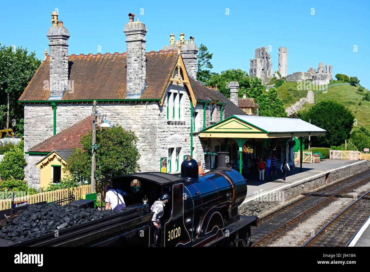 LSWR T9 Class 4-4-0 steam train entering the railway station with the castle to the rear, Corfe, Dorset, England, - Stock Image