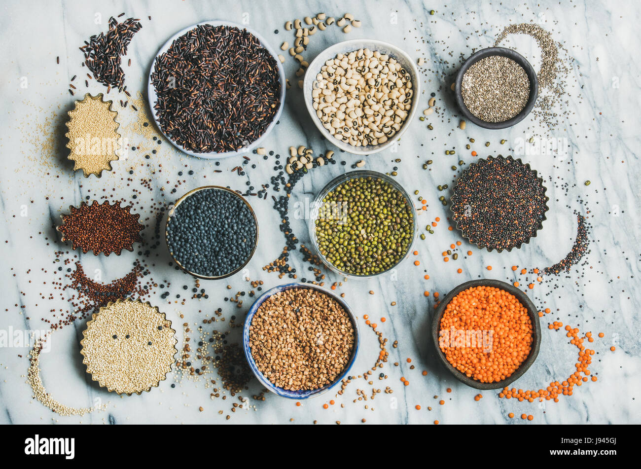 Variety of raw grains, beans, cereals over marble background - Stock Image