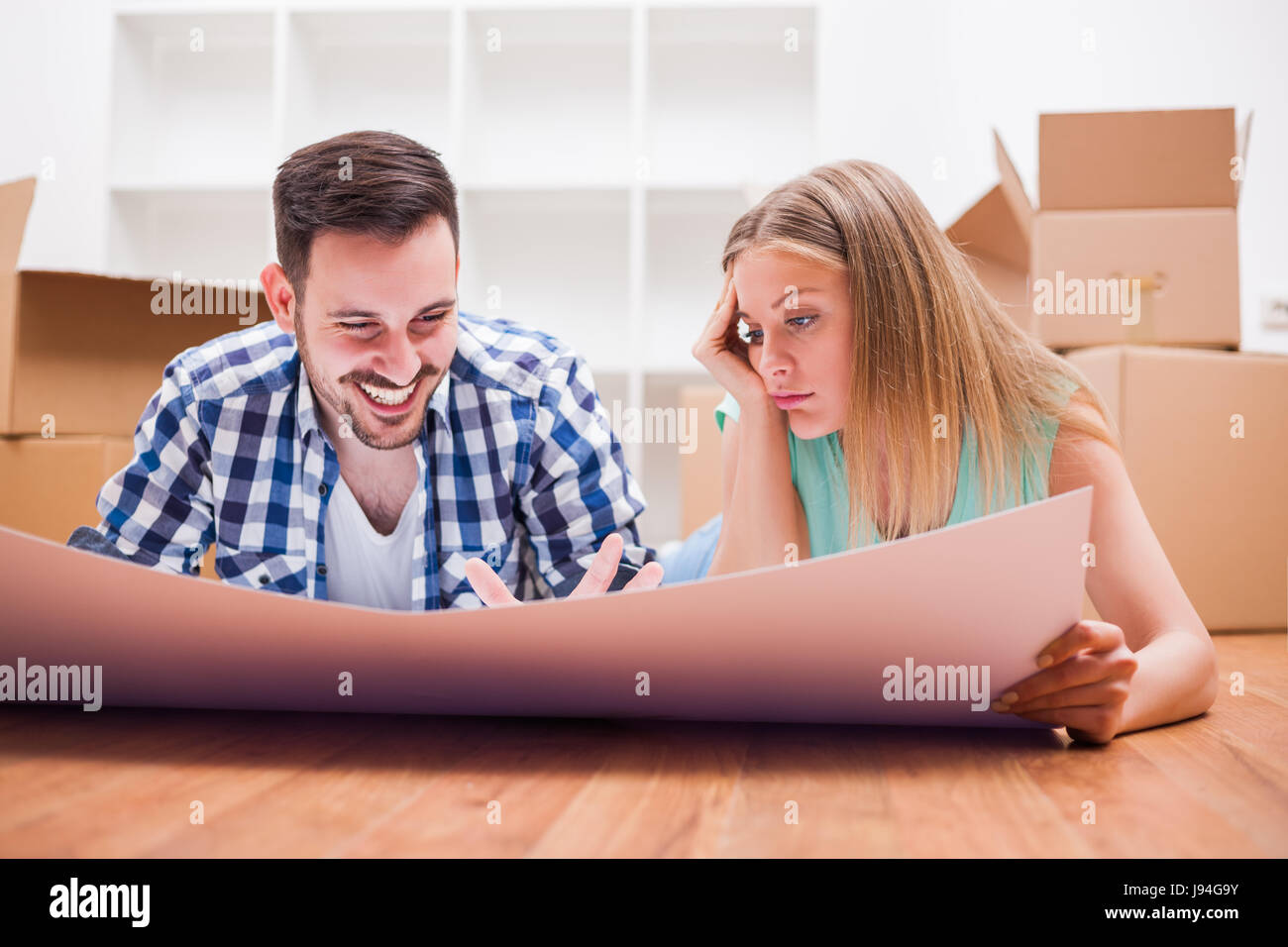 Young couple is moving in their new home. It's time for unpacking. - Stock Image
