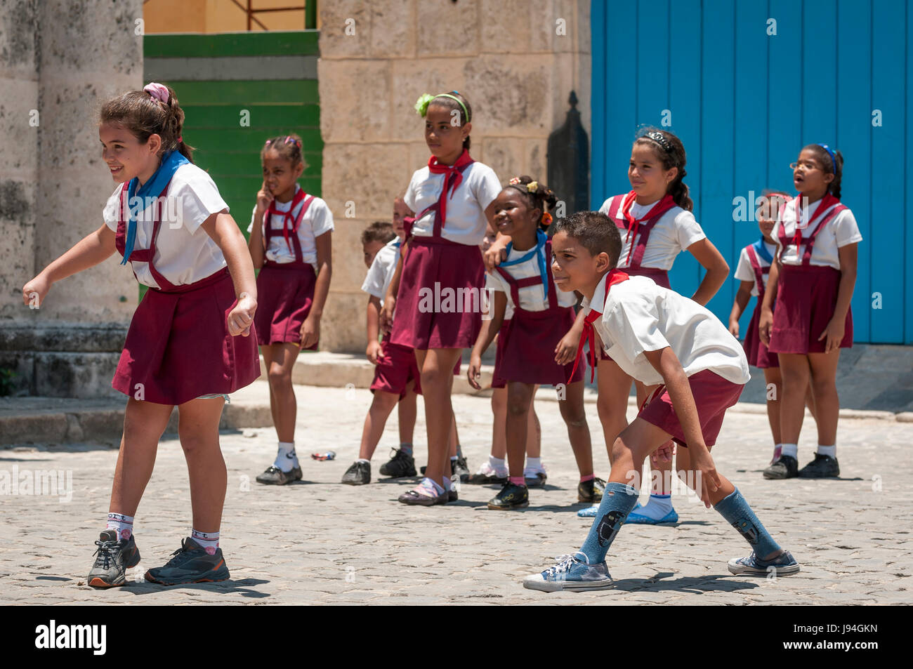 HAVANA - CIRCA JUNE, 2011: A group of school children play games on the cobblestones of a courtyard in the historic - Stock Image