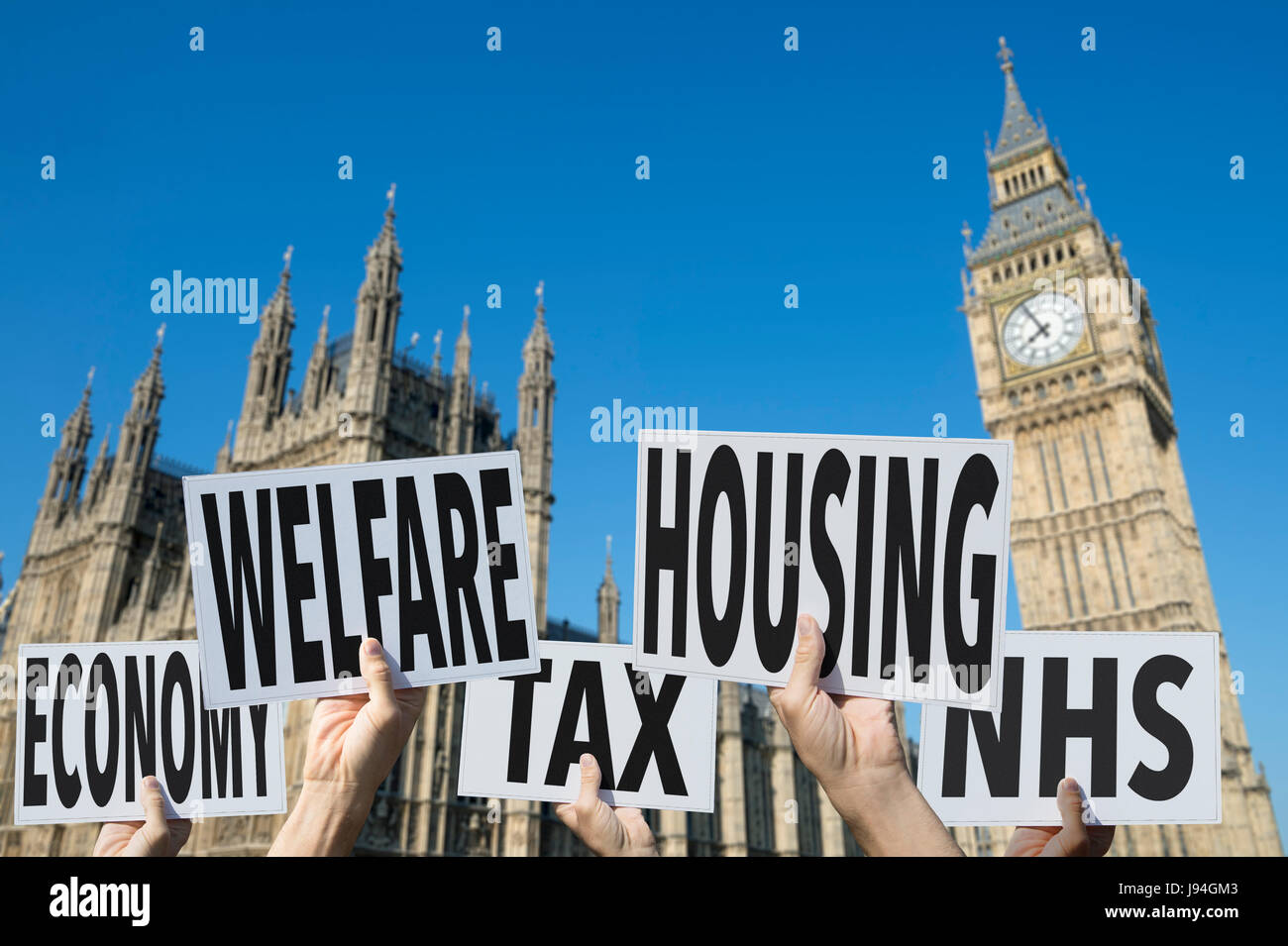 Hands holding election signs protesting modern British social issues of economy, tax, welfare, housing, health at - Stock Image