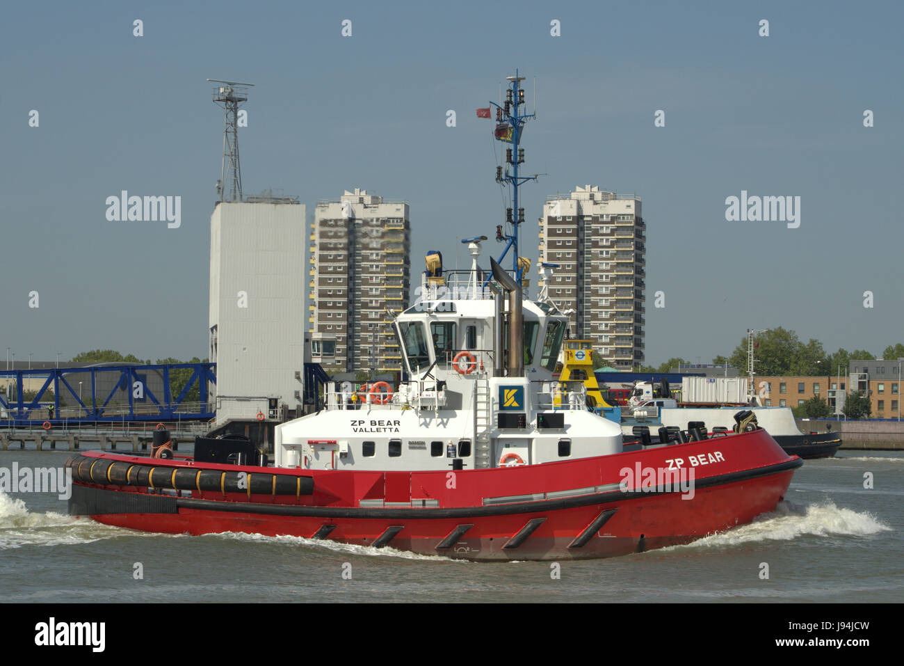Tug ZP Bear heads down the Thames in London after assisting a vessel to undock - Stock Image
