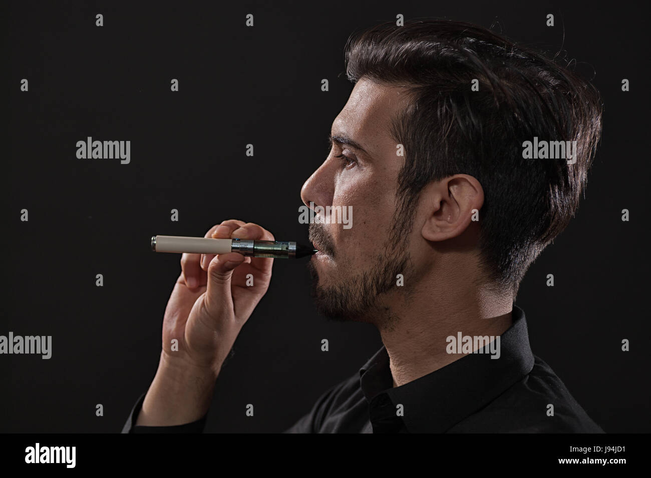 Portrait of man who is smoking electronic cigarette. - Stock Image