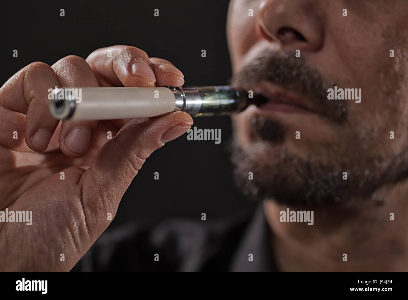 Close up image of man who is smoking electronic cigarette. - Stock Image