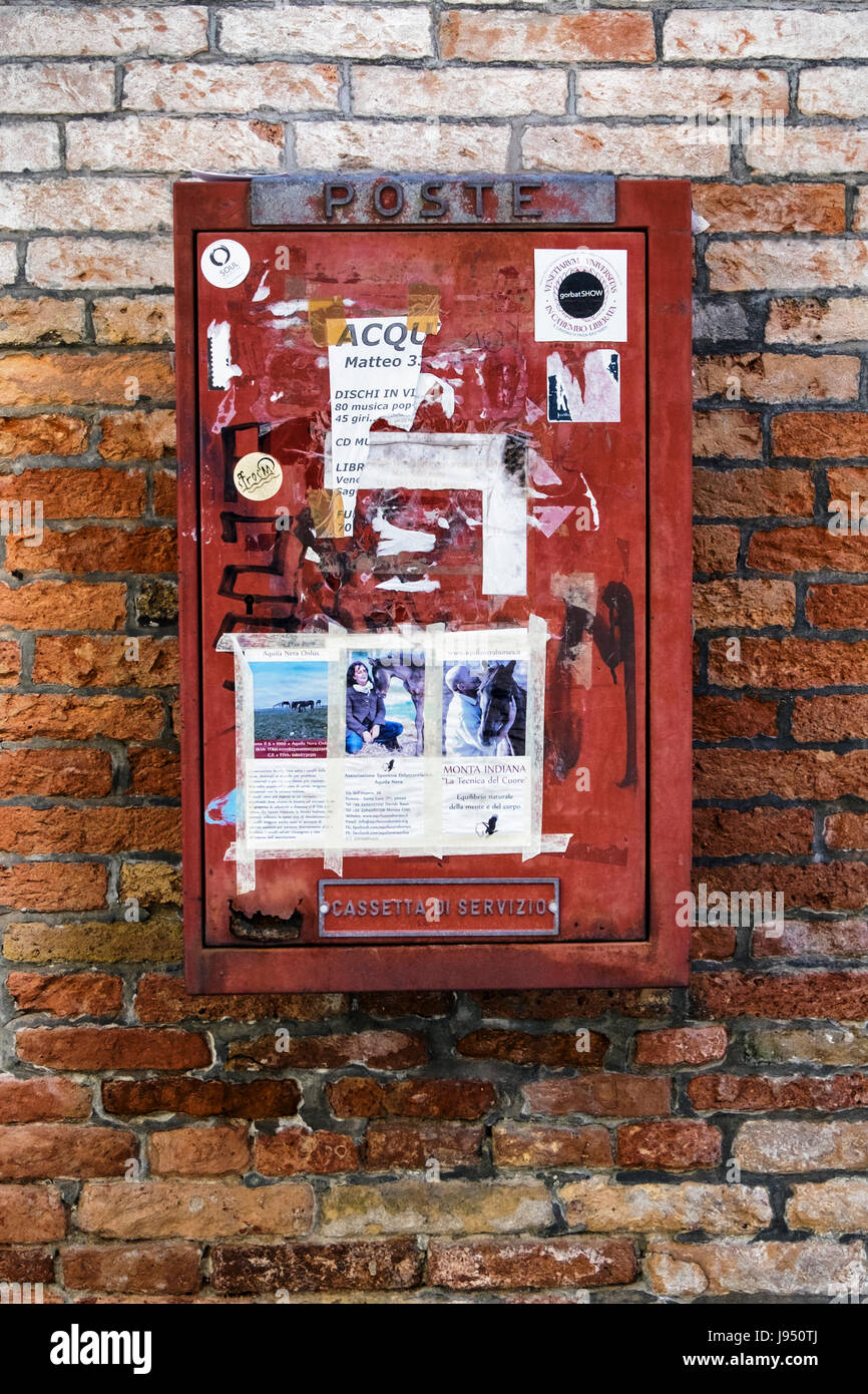 Red Venetian post box covered in stickers,Mail box,postal service - Castello,Venice,Italy - Stock Image