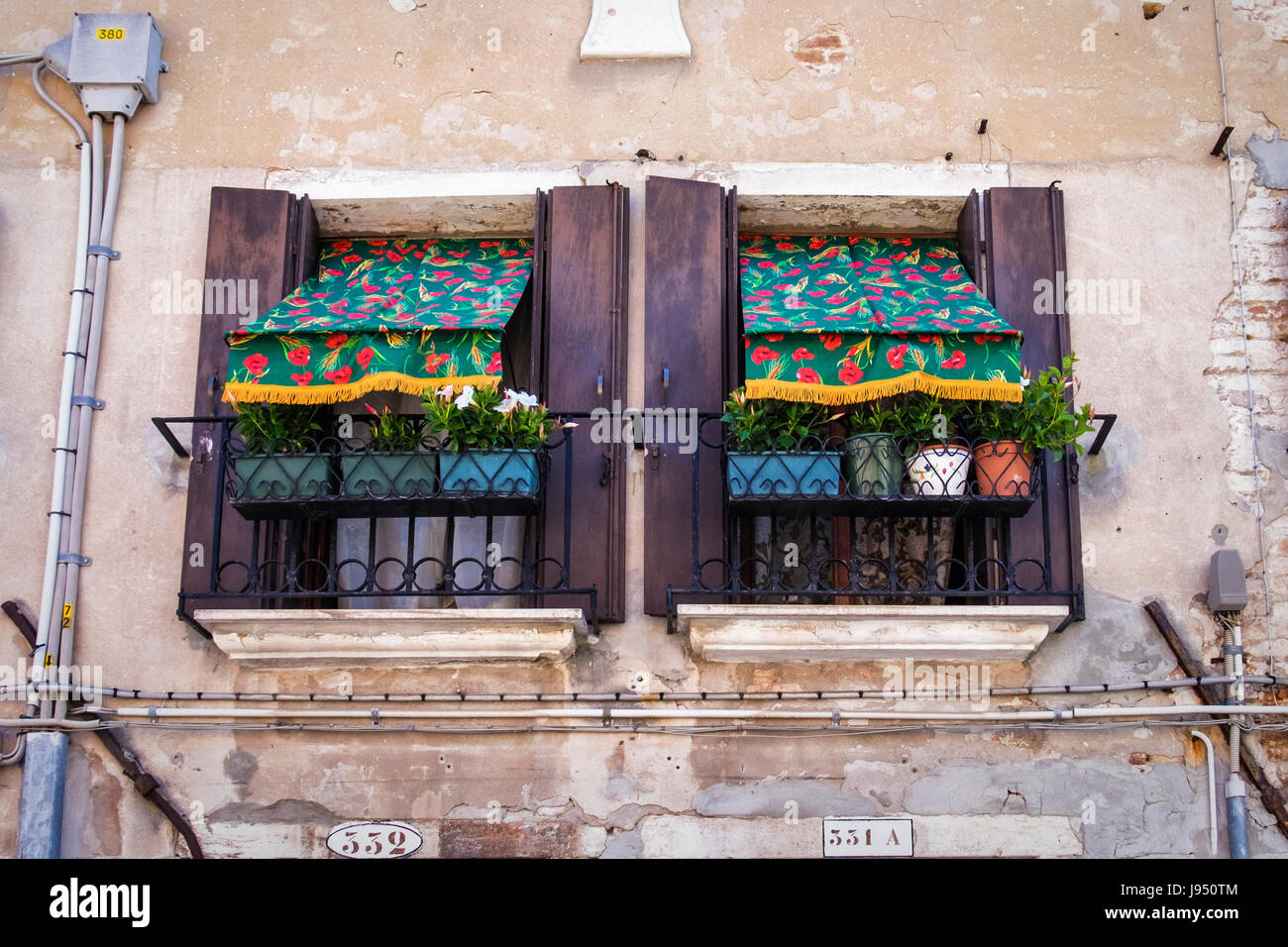 Venice,Castello,Urban landscape,Venetian house detail,windows with flower pattern awning,flower pots,Wrought iron - Stock Image