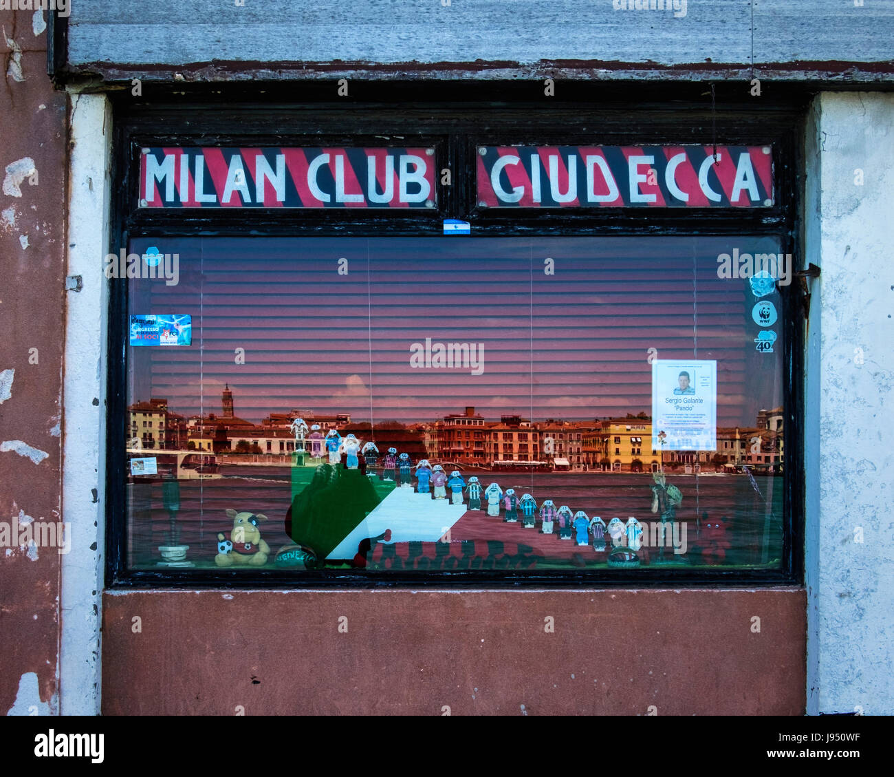 Venice,Giudecca.Milan Club, exterior window.Football supporters club wih mementoes and reflections of grand Venetian - Stock Image