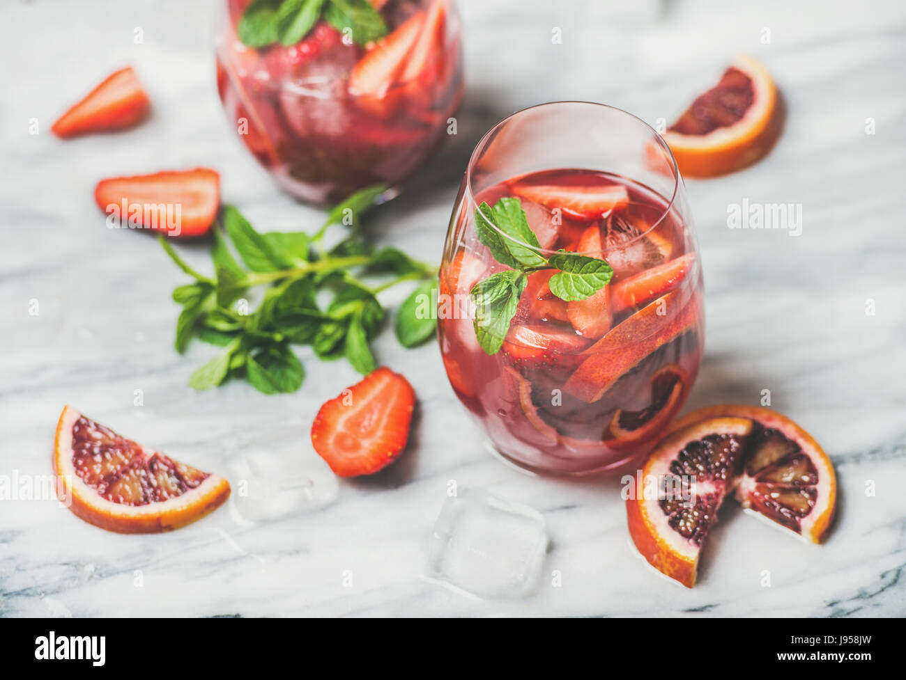 Fruit refreshing Sangria cocktails with ice and mint, marble background - Stock Image