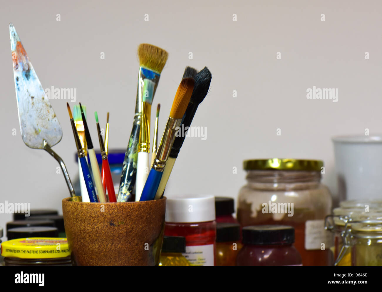 Multicolored brushes and paints in an artists' studio. - Stock Image