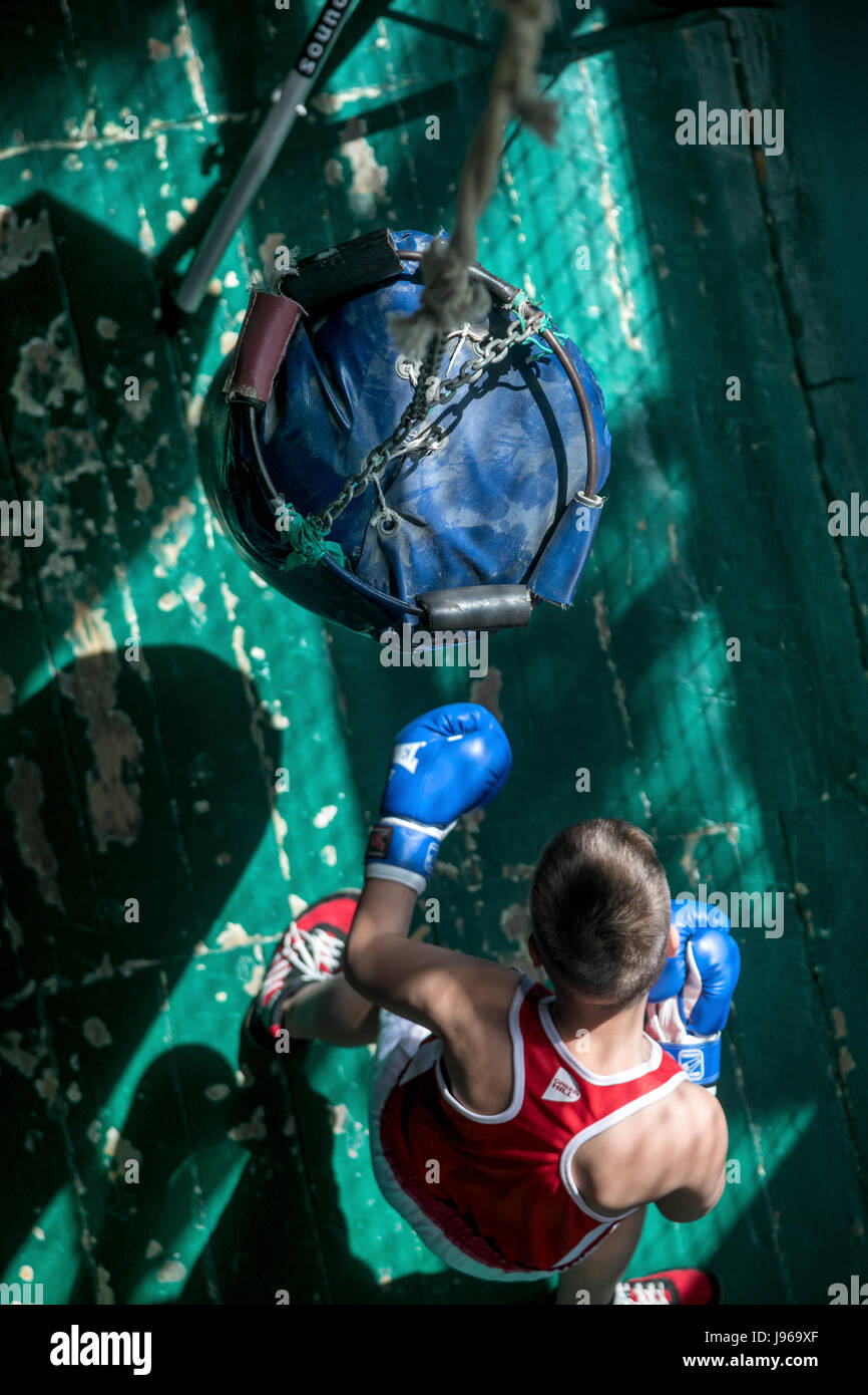 A young boxer trains with a punching bag in a gym of sports school - Stock Image