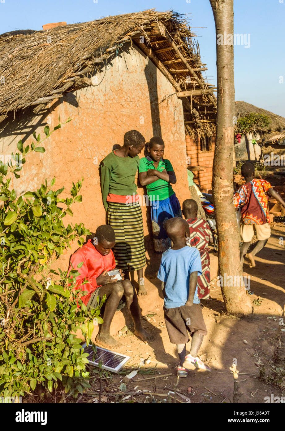 Malawian children stand by traditional grass roofed house in rural village of Kanyama, Malawi, Africa - NB Solar - Stock Image