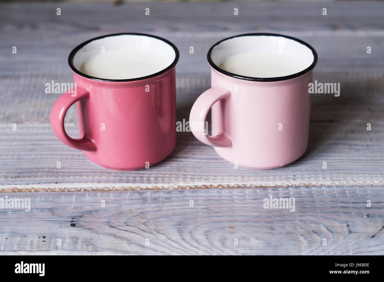Two pink cups with milk on the white wooden table - Stock Image