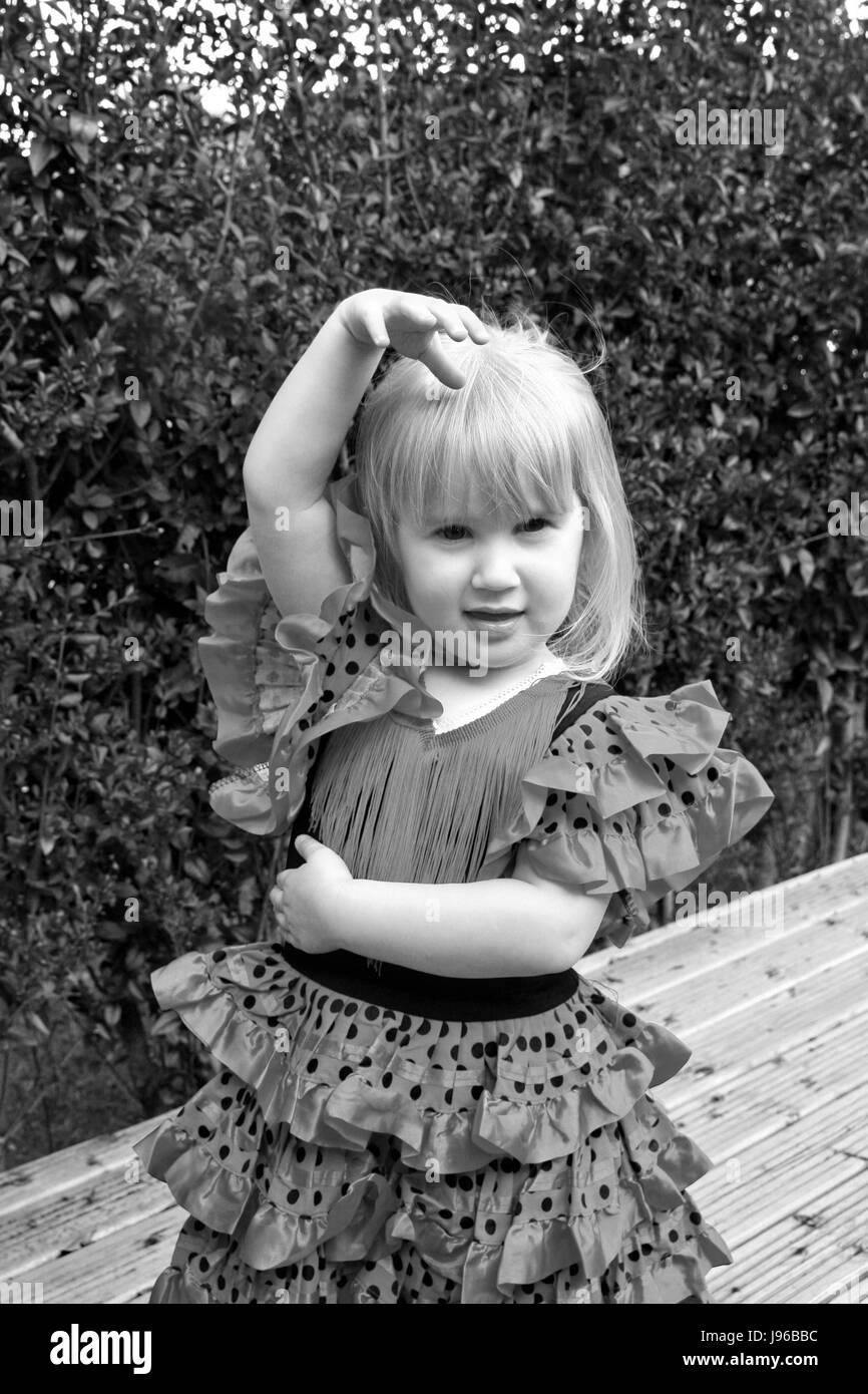 Little girl , child in a spanish dancer pose wearing a spanish dancer flamenco dress in the garden - Stock Image