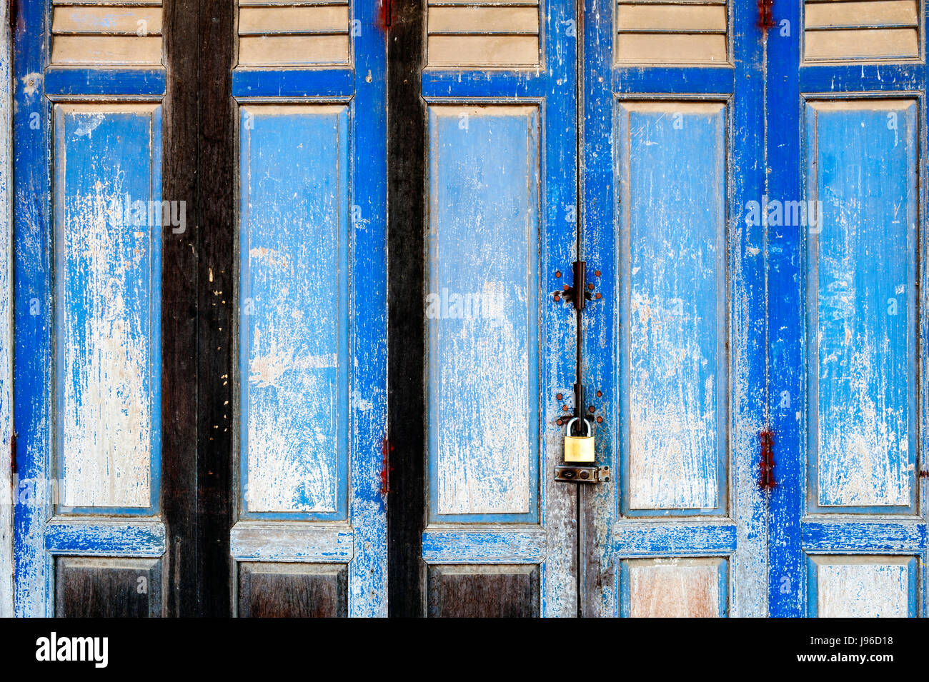 Background texture on old rustic blue wooden folding door of classic Sino-Portuguese architectural style shophouse Stock Photo