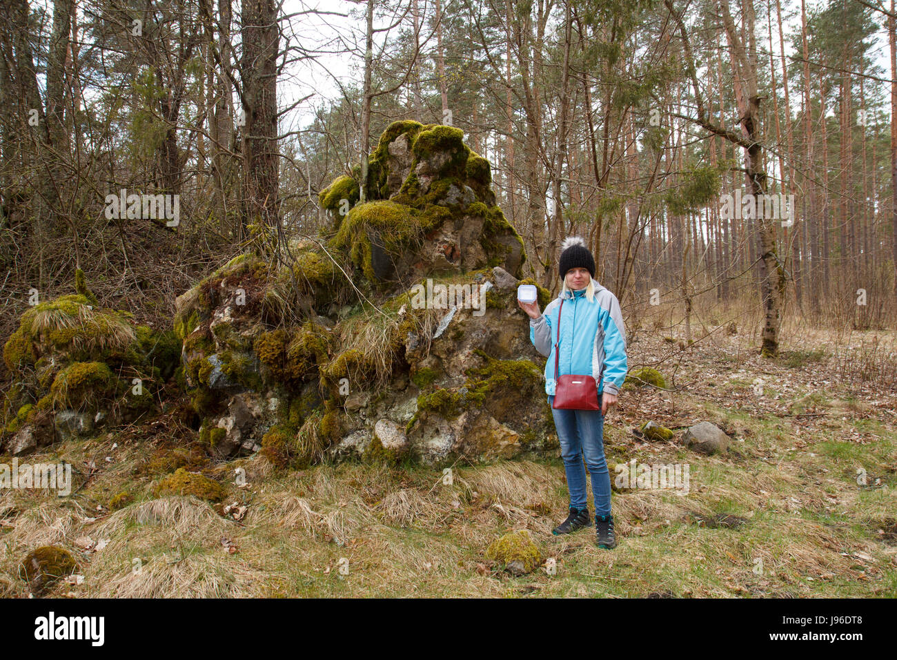 A female geocacher holding a box by a big rock - Stock Image