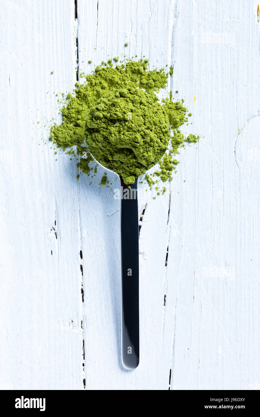 teaspoonful matcha tea on white wooden background - Stock Image