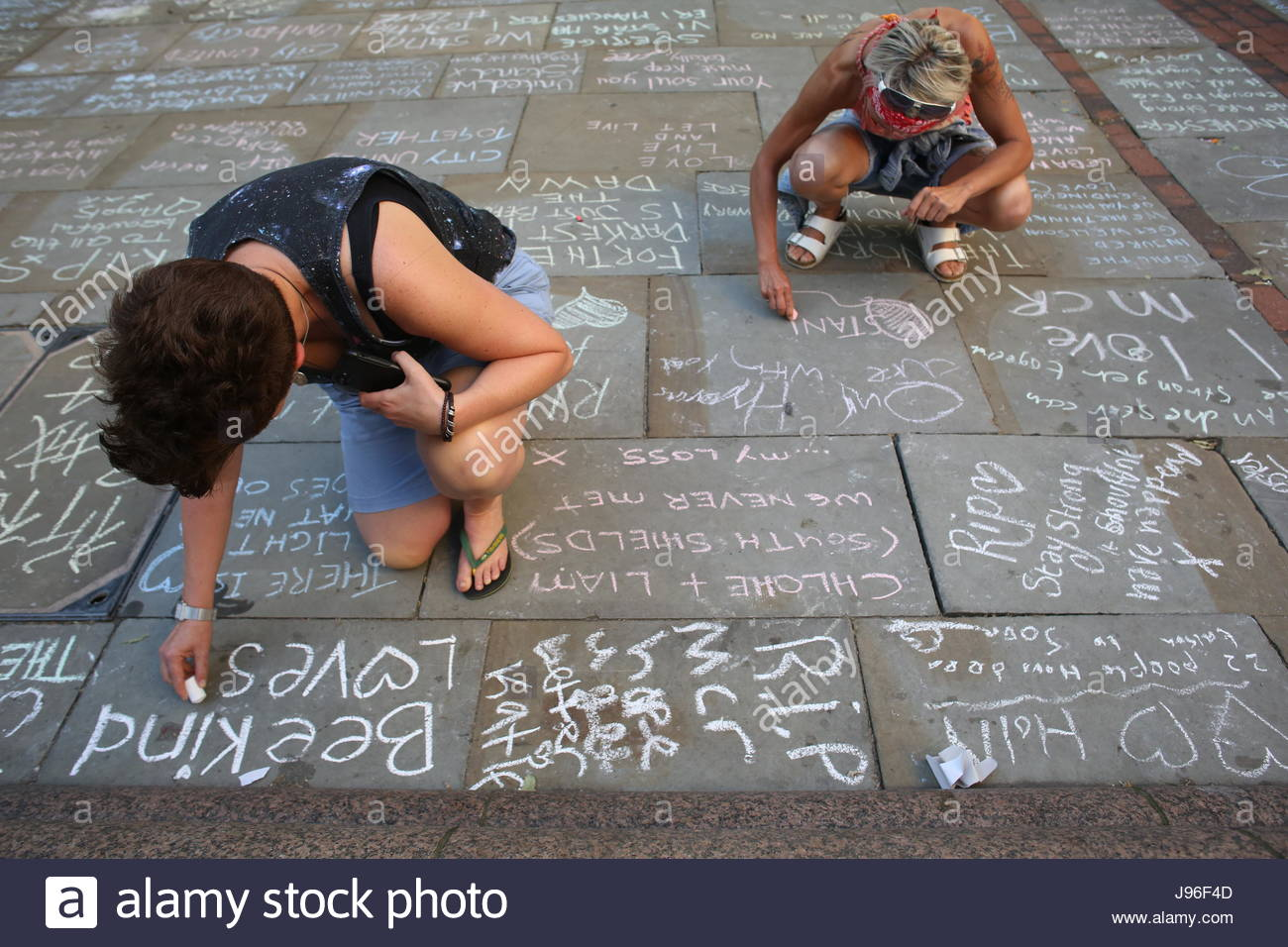 Two women chack messages of support and condolence on the street for the victims of the Manchester bombing in St - Stock Image