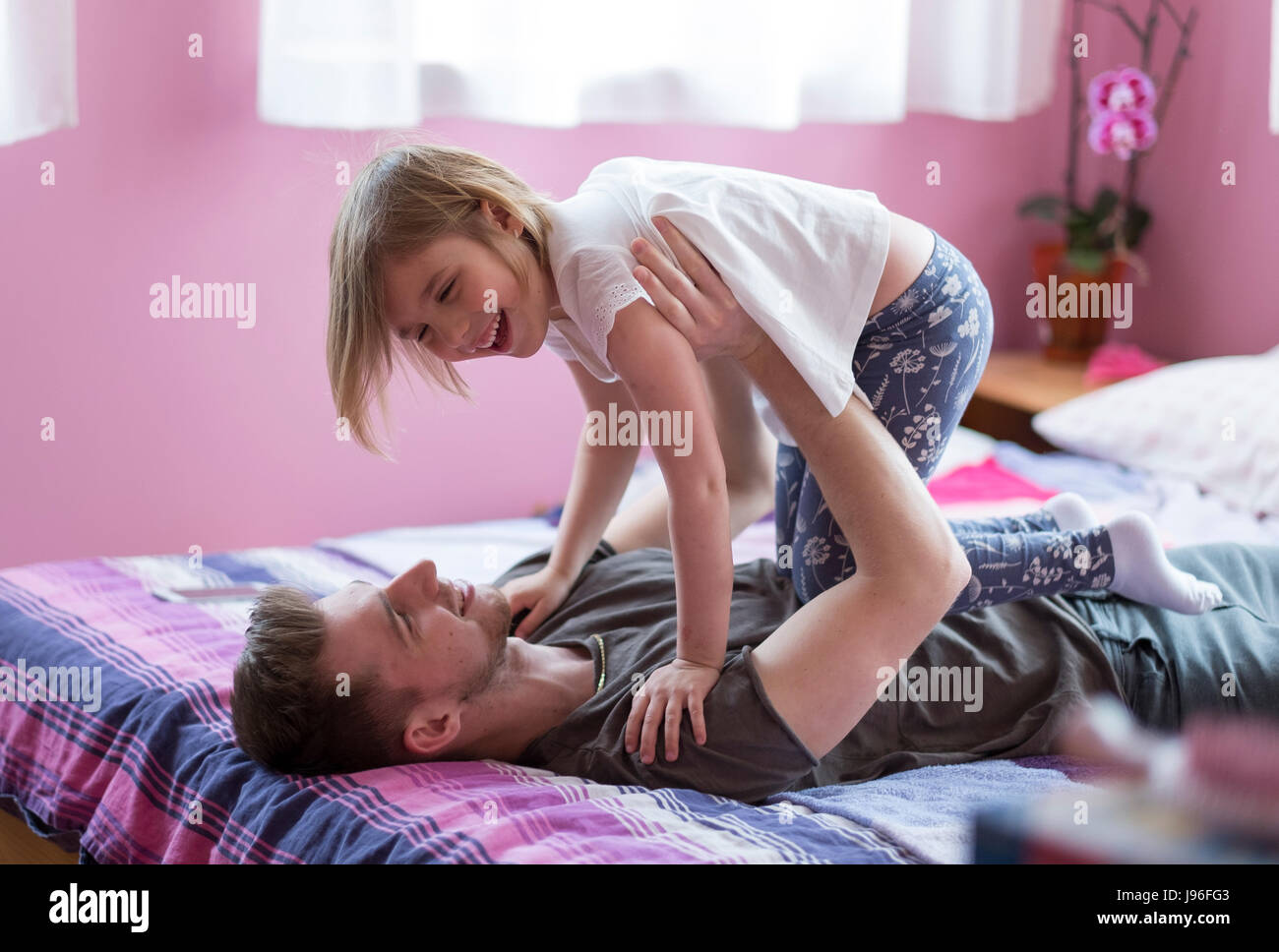 Brother and sister playing in bed - Stock Image