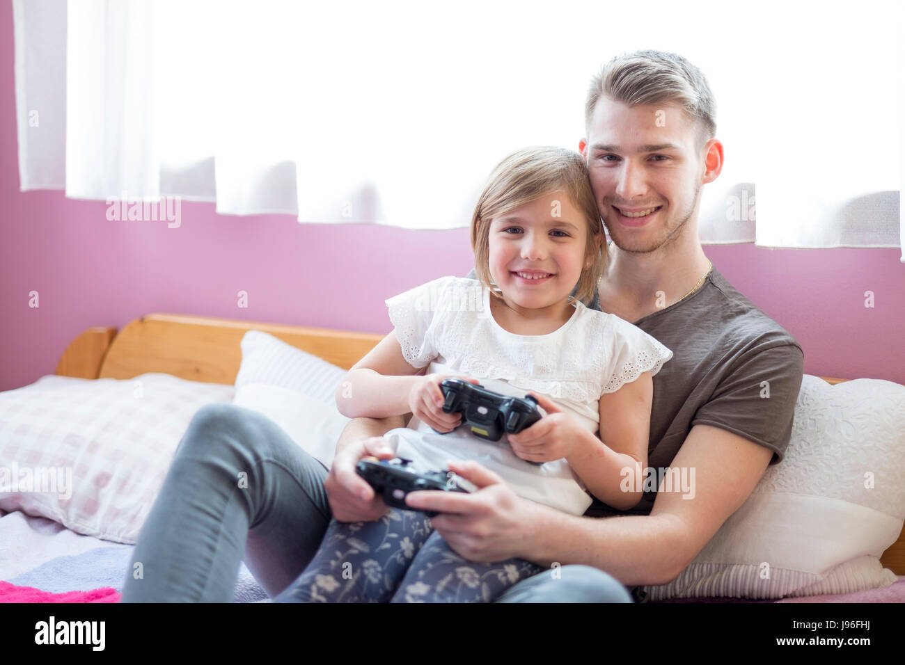 Brother and little sister playing in bed Stock Photo