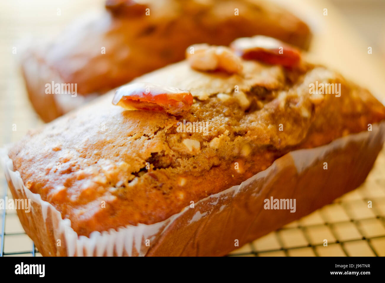Home cooked food. Two date and walnut cakes on a cooling rack. - Stock Image