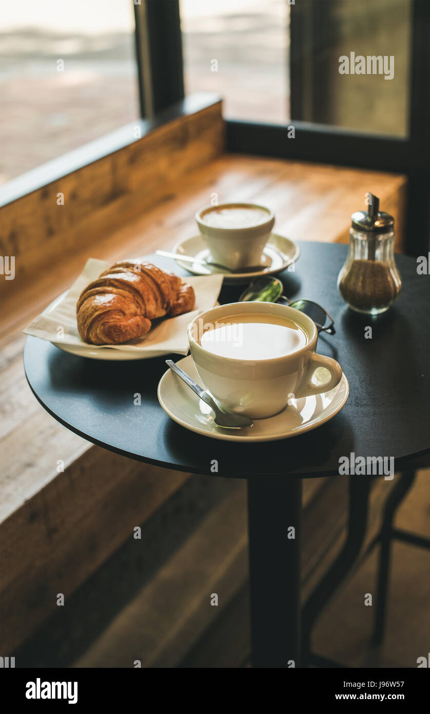 Coffee latte, cappuccino and croissant on small table in cafe - Stock Image