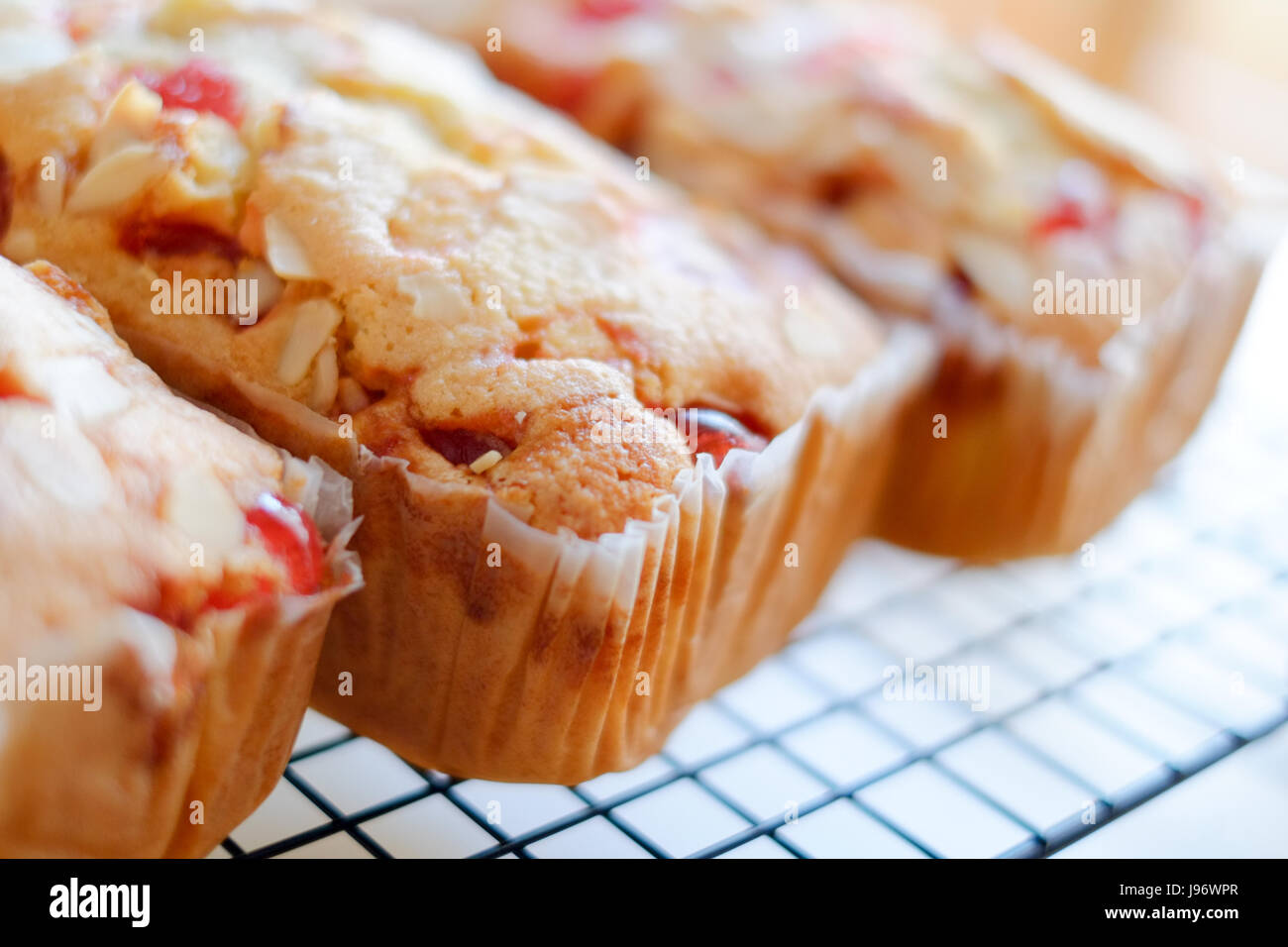 Home cooked food. Three cherry and almond cakes on a cooling rack. - Stock Image