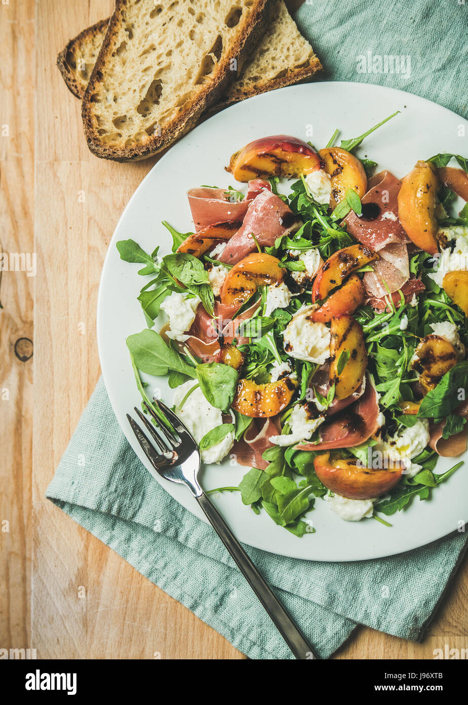 Arugula, prosciutto, mozzarella and grilled peach salad in white plate - Stock Image
