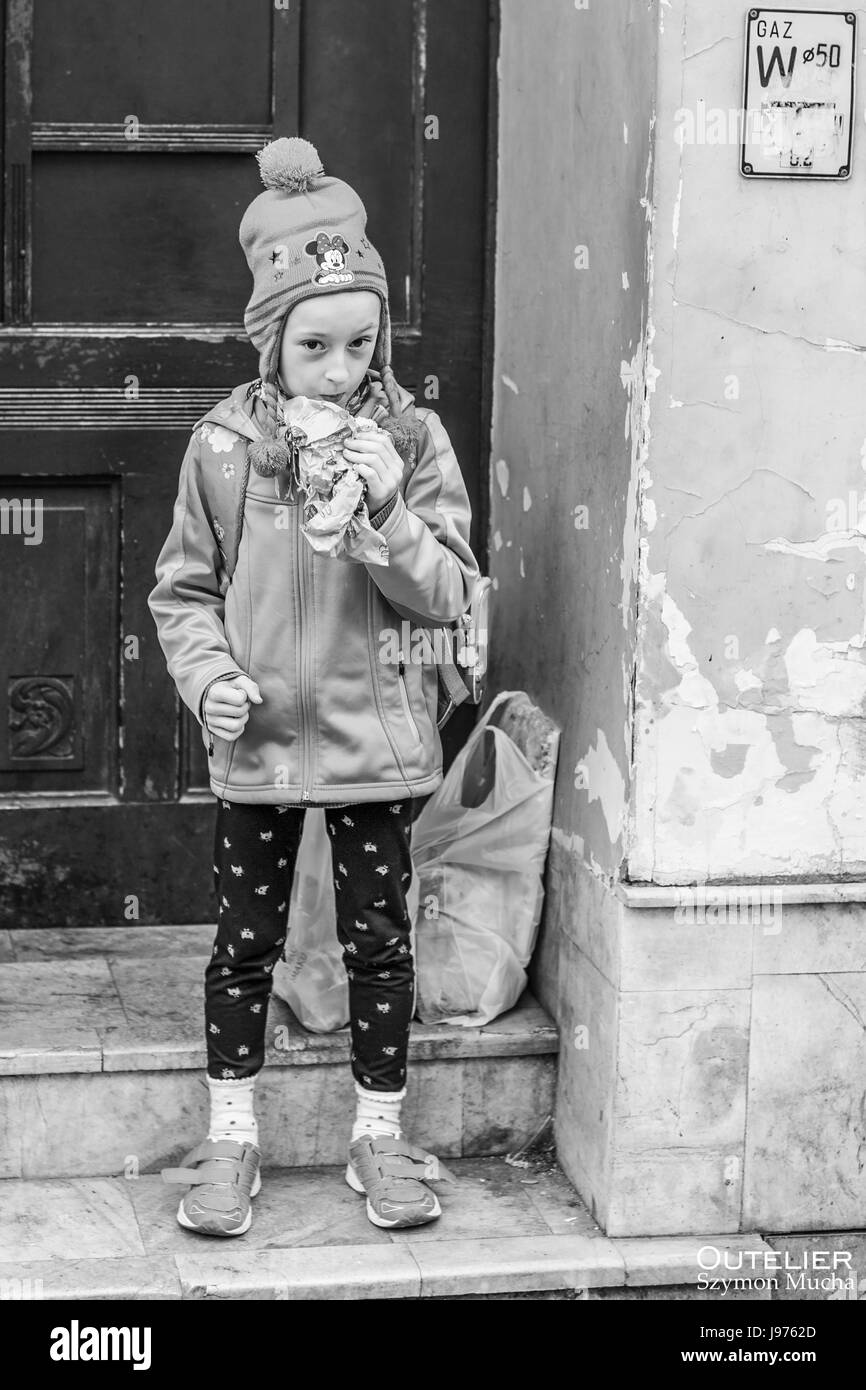 A girl in school age having her elevenses. Torun, Thorn, Poland. Black and white photography. - Stock Image