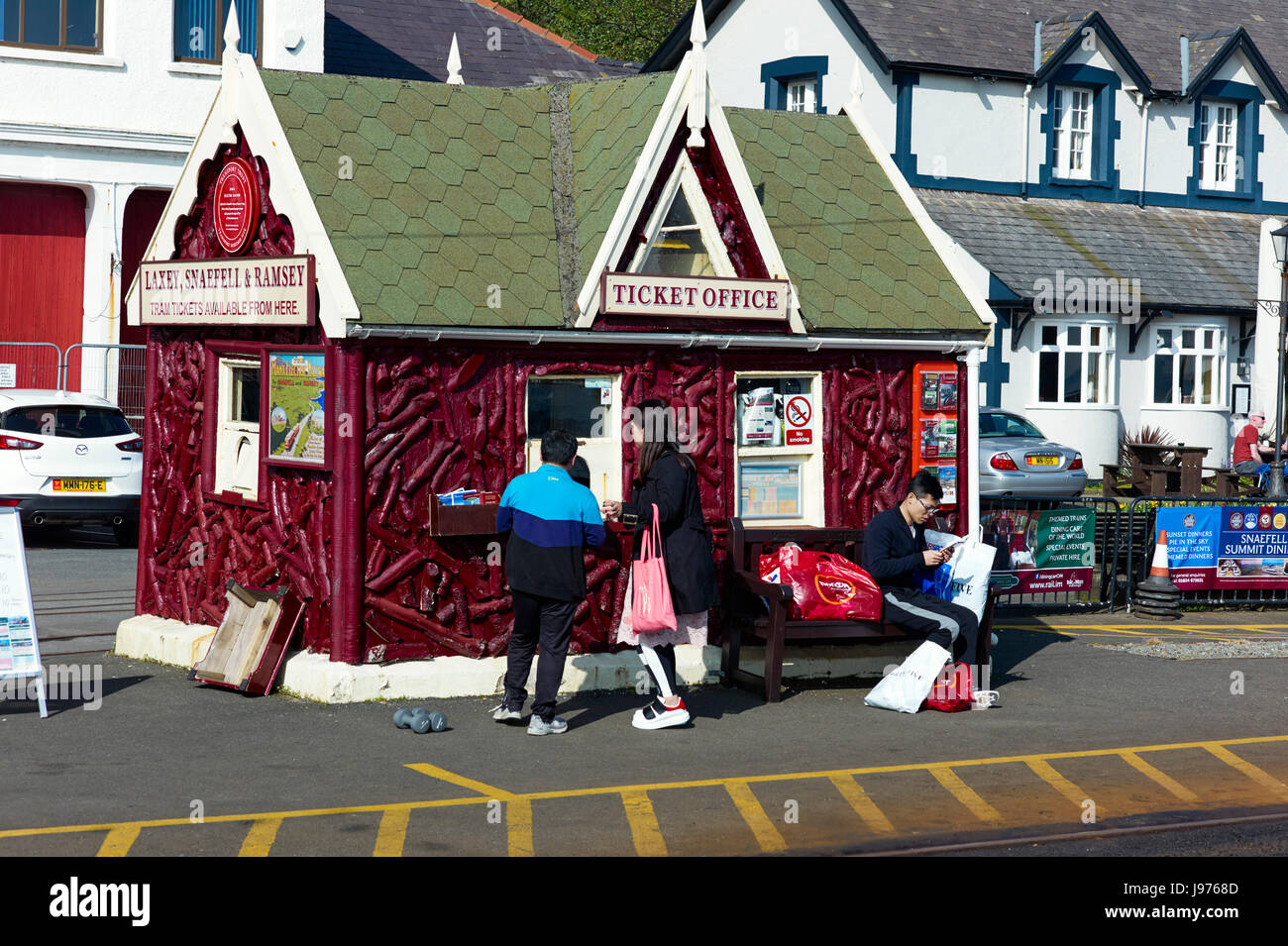 Asian tourists buying tickets for Manx Electric Railway in Douglas, Isle of Man - Stock Image