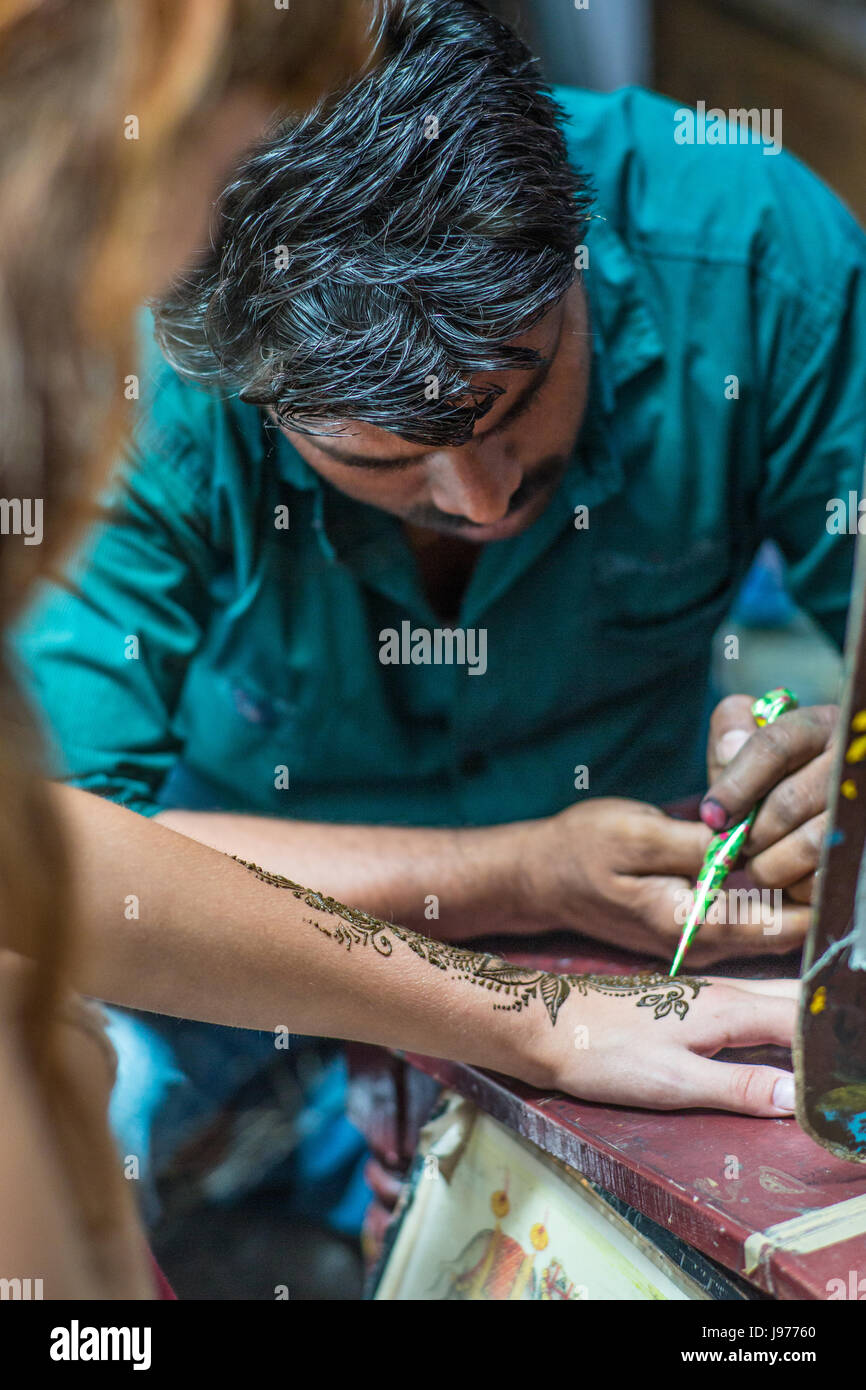 Woman receiving henna hand paintings by a Indian man. - Stock Image