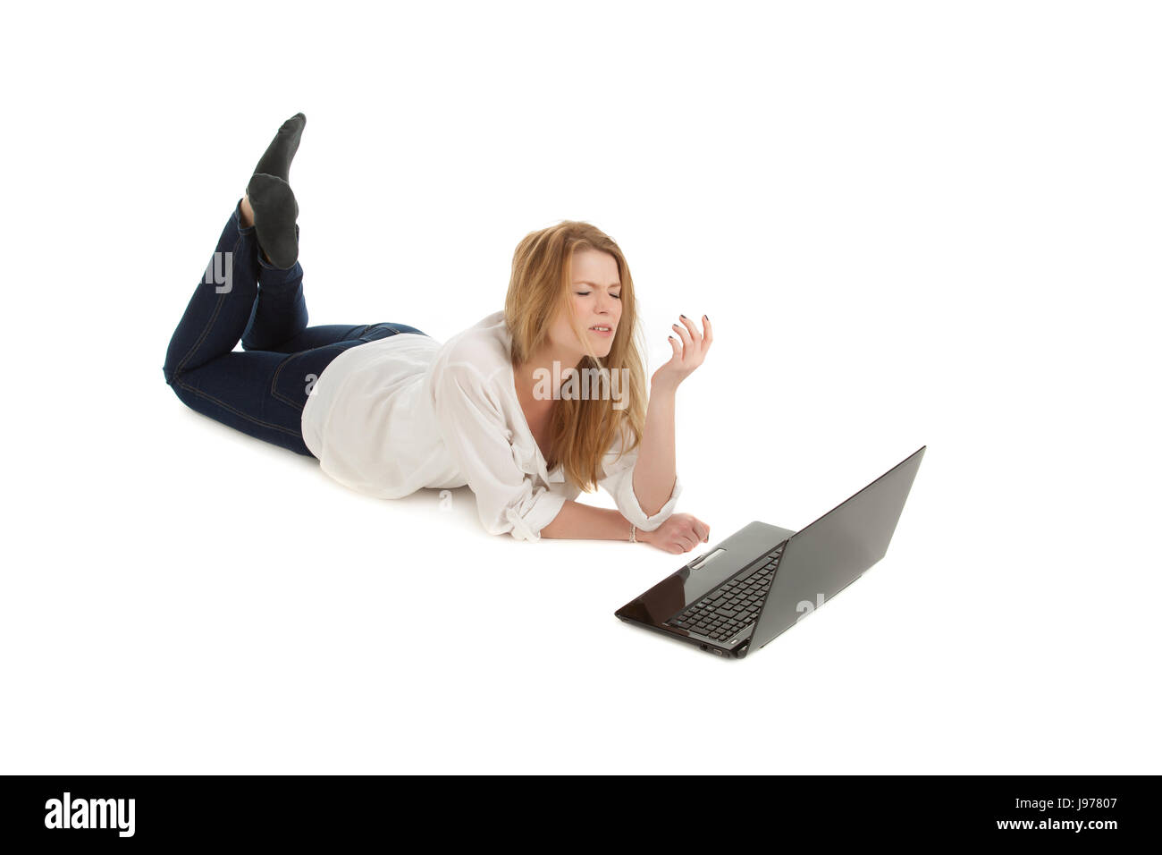 young blonde woman lying down with computer - Stock Image