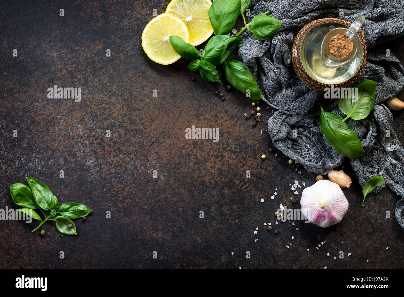 Ingredients for cooking - garlic, lemon, basil, spices and olive oil. Food background on the kitchen table. Top - Stock Image