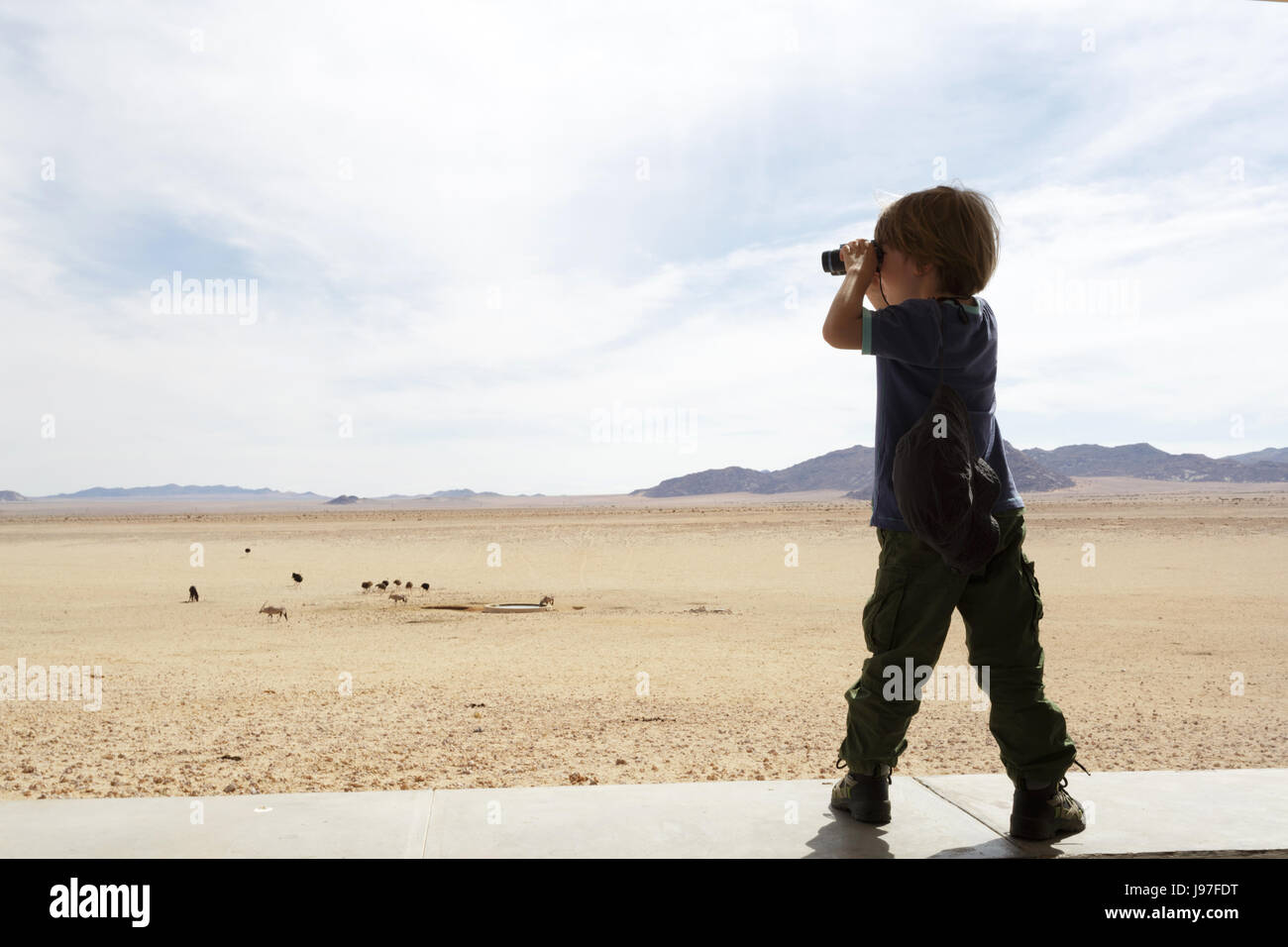 Young boy looking wit a binocular at wildlife in Garub viewpoint, Namibia. - Stock Image