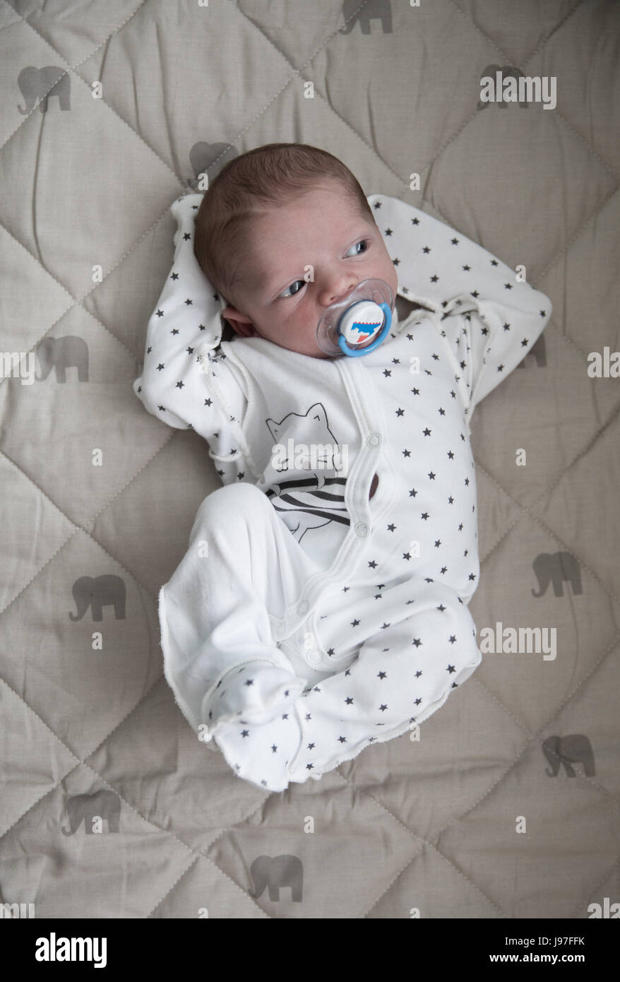 Pensive new born baby boy is laying in white sleepers with blue nipple and watching int the window - Stock Image