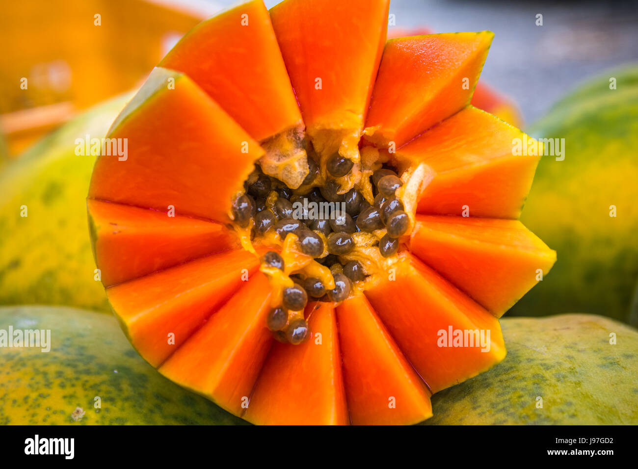Closeup of bright orange papaya cut artfully with brown seeds surrounded by light green skinned whole papayas in - Stock Image