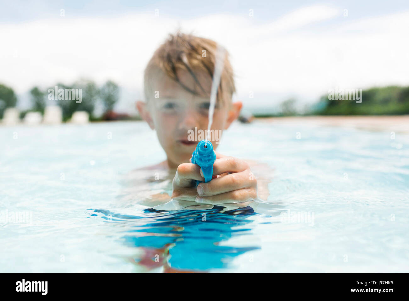 Boy (6-7) playing with squirt gun in swimming pool - Stock Image